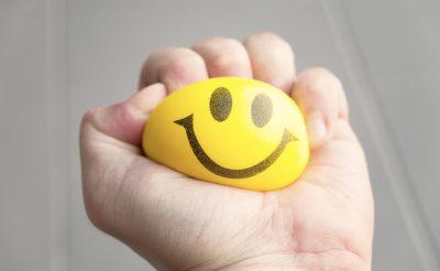 יד לוחצת על כדור צהוב שיש עליו סמיילי
